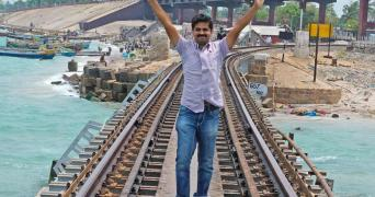 Basheer stands on a railway track running over the sea, wearing a light violet shirt with both his arms raised up