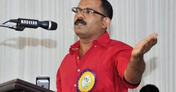 KM Shaji wearing a red shirt and speaking at an event standing
