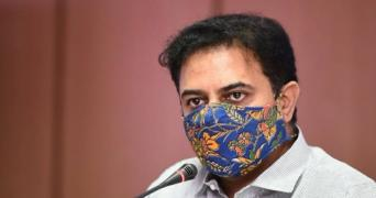Telangana Industries Minister KT Rama Rao wearing a mask with a blue print, speaking into a mic