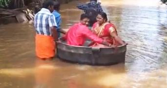 The couple, decked up in pink wedding attires, sit in a copper cooking vessel to travel through a flooded road. Three people are seen steering the vessel through the water.