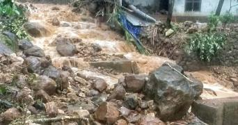 Landslide with mud water gushing down threw rocks behind which is a house partially visible