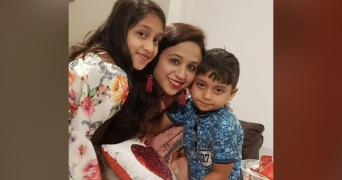 Seema Banu Syed is hugging her two children. She is wearing a green saree and red earrings