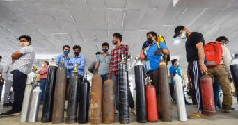 A group of people, each standing with holding an oxygen cylinder outside a hospital