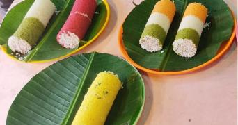 Three plates with leaves carrying colourful puttu