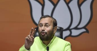 Prakash Javadekar gesticulates with his right hand while speaking to the media at the BJP office, the party's lotus symbol in the backdrop