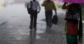 Women standing on road holding umbrella in rain
