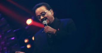 SP Balasubrahmanyam singing at an event wearing a dark coat, light only on his face, mic held in left hand