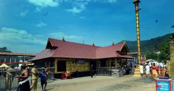 A view of the Sabarimala temple under a darkening blue sky with a few people on one side