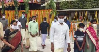 A group of TTD employees and their family members wearing masks and walking inside the Tirumala temple premises