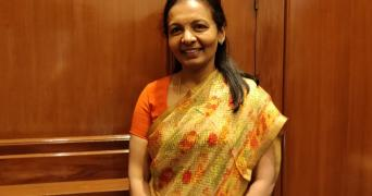 Valli Arunachalam wearing an orange saree, standing against wood paneling