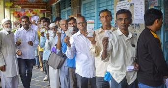Voters standing in a queue with their ID proof in hand