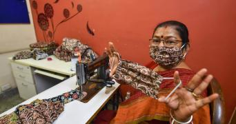 A woman in New Delhi holds up a cloth mask that she stitches and distributes for free