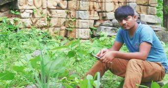 A file photo of Aravind Pakide wearing a blue shirt and brown pants, surrounded by greenery