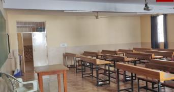 An empty classroom equipped with sanitizer dispenser