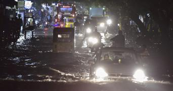 Several vehicles seen moving slowly on a road inundated due to Cyclone Nivar
