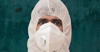 A healthcare worker with mask and coverall PPE