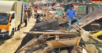 Man wearing blue shirt stands around debris