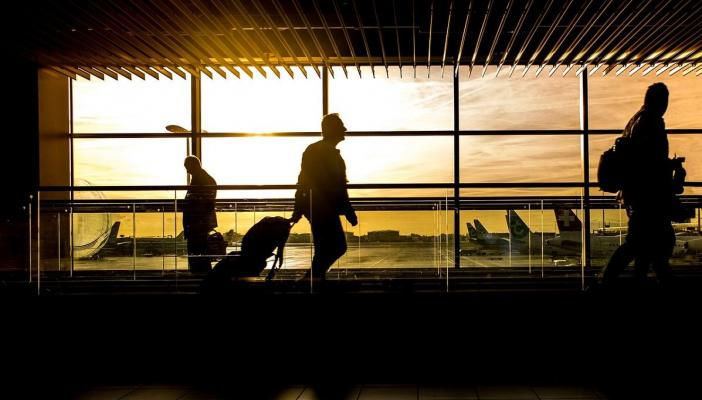 The silhouette of a man walking across a window with his suitcase at an airport