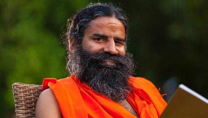 Holding a book, Ramdev poses for a photo