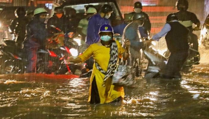 Woman crossing in knee-deep water in Bengaluru's KR Market