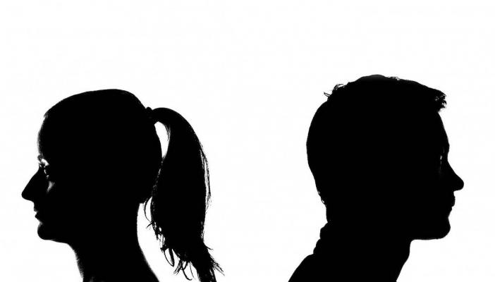 A man and a woman stand back to back in black and white image