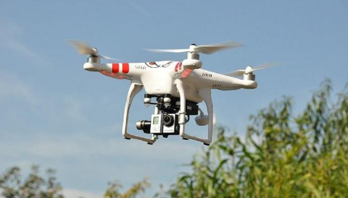 A white-coloured drone with a camera attached in the air