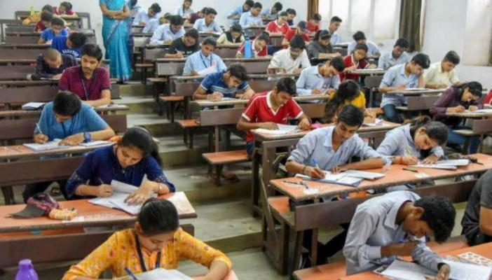 Students sit on benches to write their exams