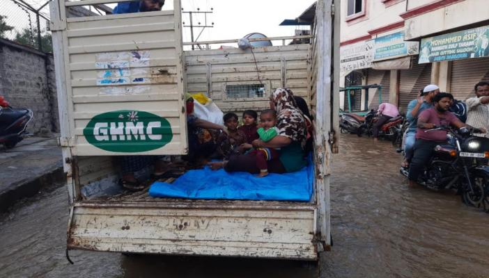 A family moves out in a GHMC garbage truck at Hafiz Baba Nagar in Hyderabad on October 19 evening