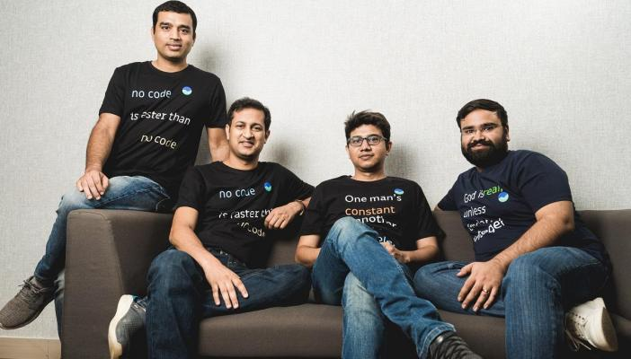 Groww's four founders sitting on a brown couch, all wearing black coloured company t-shirts.