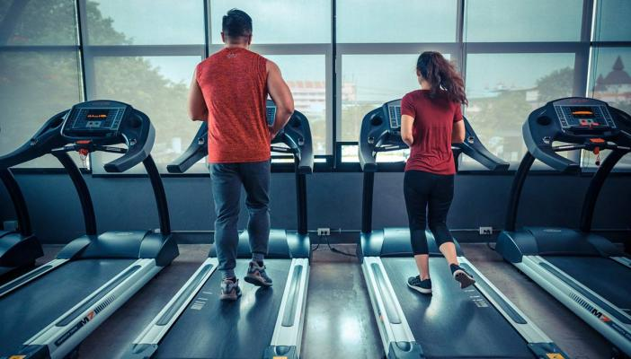 A man in red and a woman in red running on a treadmill at a gym while facing their back towards us