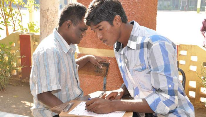 A scribe writing the exam for a student with visual disability