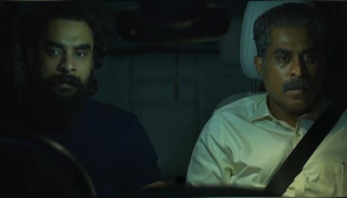 Tovino Thomas and Suraj Venjaramoodu sitting next to each other in the front seats of a car in Kaanekkaane