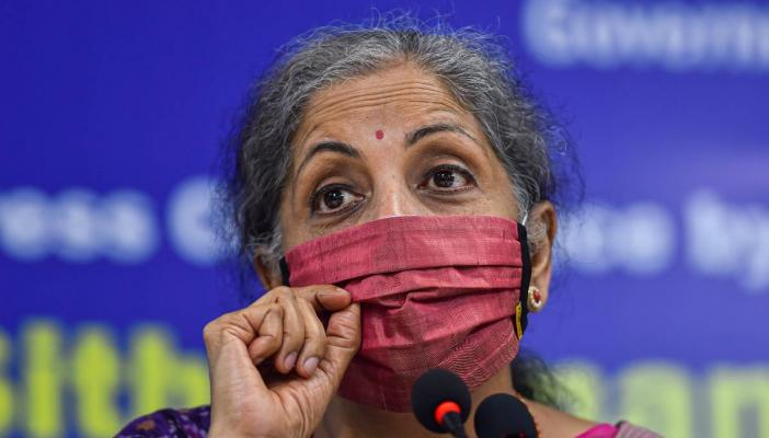 Finance Minister Nirmala Sitharaman wearing a pink mask speaking at an event, close up photo