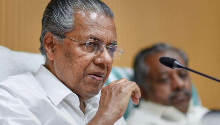 Kerala Chief Minister Pinarayi Vijayan wearing a white shirt addresses a press conference