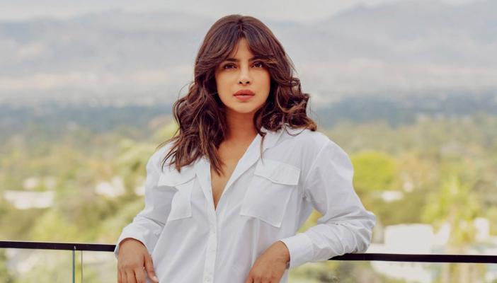 Actor Priyanka Chopra posing in a white full-sleeve shirt