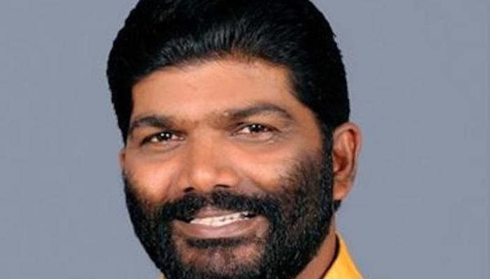 Radhakrishnan in orange shirt, beard, smiles, against a grey background