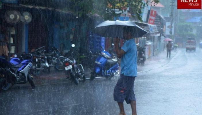 A man walking across a street holding a black umbrella in the rain