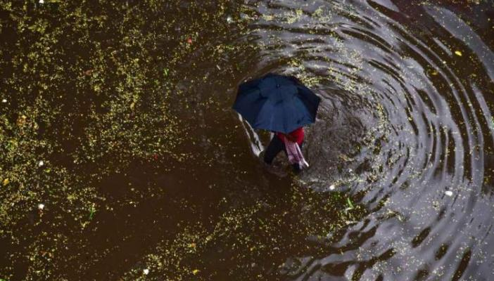 A man with an umbrella walking in a pool of water