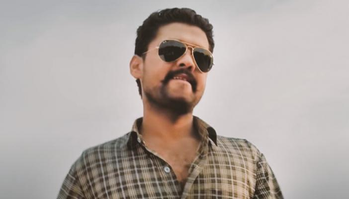 Rakshit Shetty in a plaid brown shirt in a still from the film Richie