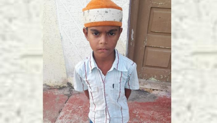 Rehan, the ten year old boy who sells bird food for her sister standing in the photo with a skull cap and a shirt
