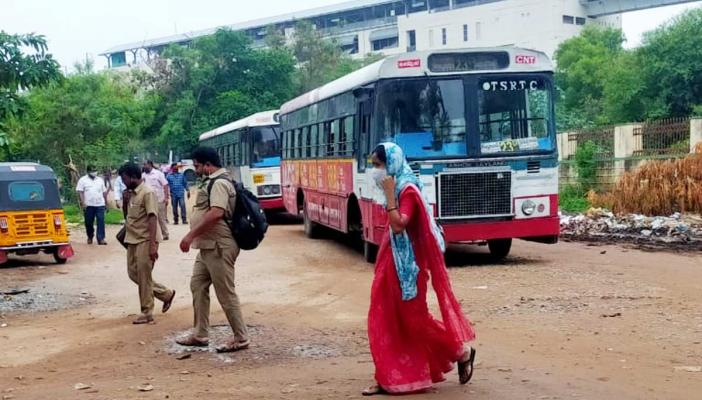 A woman conductor dressed in a saree walking inside a TSRTC depot along with male conductors