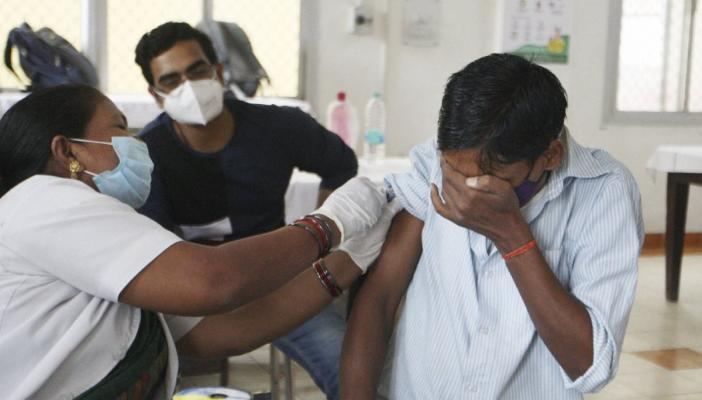 A beneficiary reacts while receiving a dose of COVID-19 vaccine