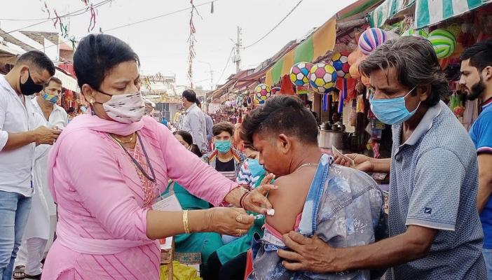 A health worker in Jammu vaccinates a young man who exposes his arm while another person holds down his shirt