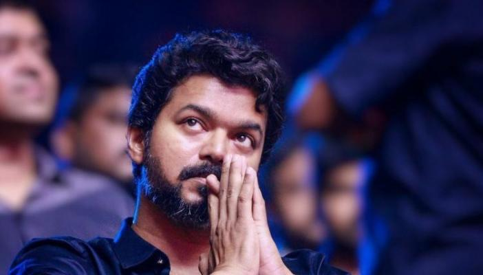 Vijay wearing a black shirt and with his hands folded