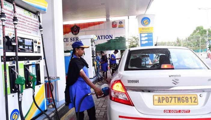 A woman attendant filling fuel in a car at a Bharat Petroleum bunk