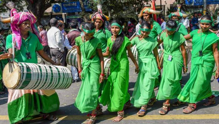 Tribals dancing on the streets in New Delhi in Green costumes