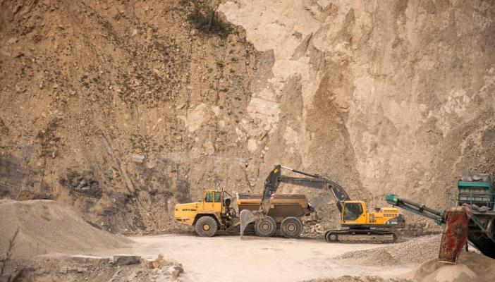 An excavator and other industrial machines in a quarry